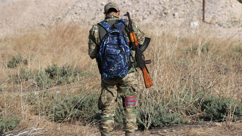 Un combatiente rebelde sirio respaldado por Turquía lleva una mochila y un arma en el pueblo de Yabisa, cerca de la frontera turco-siria, Siria, 13 de octubre de 2019.