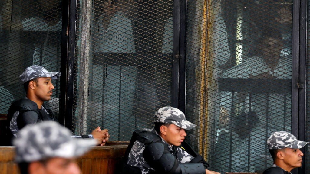 Policías sentados en la corte mientras se ve a los sospechosos detrás de una reja en El Cairo, Egipto. 28 de julio de 2018.