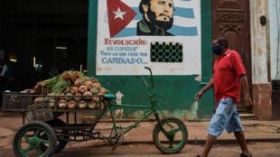 """Un hombre con una mascarilla camina cerca de un letrero con la imagen del difunto líder cubano Fidel Castro y en donde se lee """"Revolución es cambiar todo lo que debe ser cambiado"""", en La Habana el 13 de mayo de 2020, en medio de la pandemia del nuevo coronavirus. Cuba lleva dos semanas con más altas médicas que contagios y arrincona a la enfermedad pero sin bajar la guardia. Hasta el momento ha confirmado 1810 casos, con 79 fallecidos."""