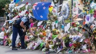 شرطي يضع الزهور أمام مركز لينوود في كرايستشيرش بنيوزيلندا 22 مارس/آذار 2019