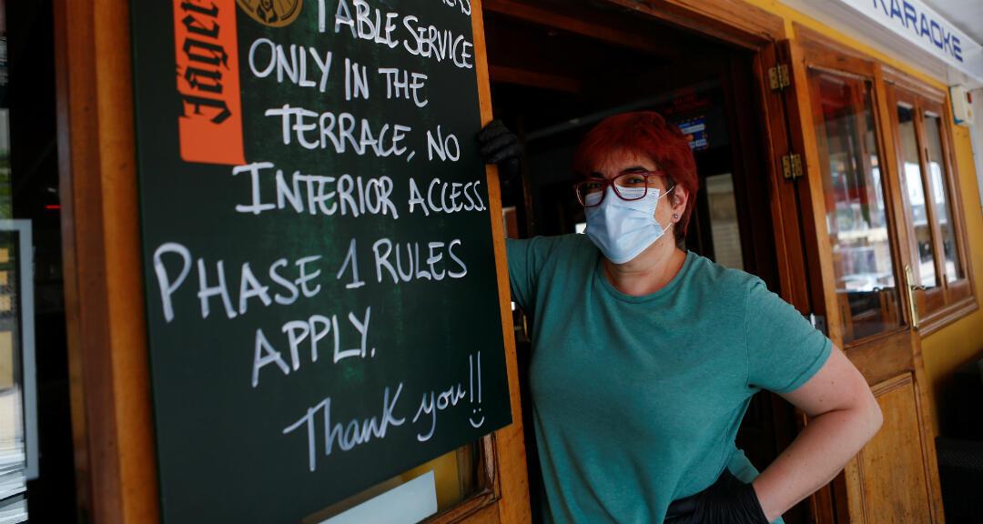 Toni, de 45 años, propietaria de un restaurante en la playa posa con mascarilla y guantes durante la reapertura de la actividad comercial tras la cuarentena por coronavirus en Mallorca, España, el 16 de mayo de 2020.