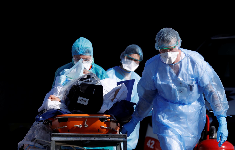 مريض مصاب بفيروس كورونا محاط بطاقم طبي قبل نقله بطائرة هليكوبترمن مستشفى جامعة ستراسبورغ إلى بفورتسهايم في ألمانيا مع استمرار تفشي فيروس كورونا، في فرنسا، 24 مارس/ آذار 2020.