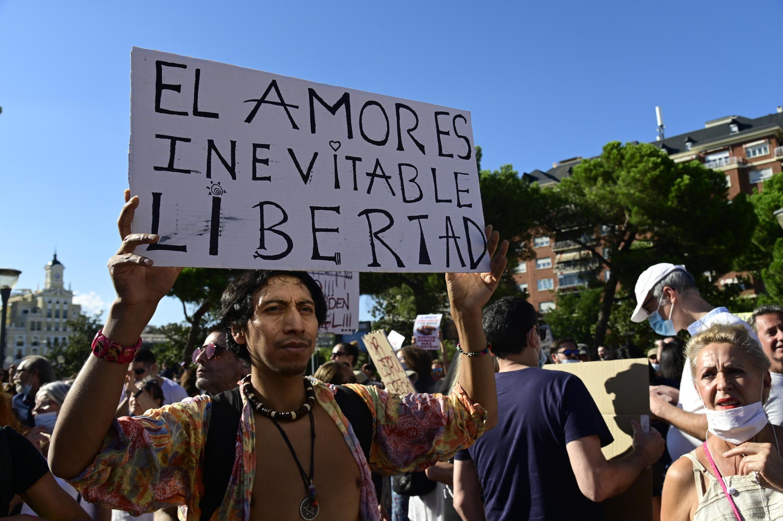 """Un manifestant anti-masque brandit une pancarte lisant """"L'amour est inévitable"""", à Madrid, le 16 août 2020."""