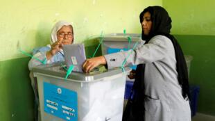 Une femme dépose son bulletin de vote, le 20 octobre 2018, à Kaboul.