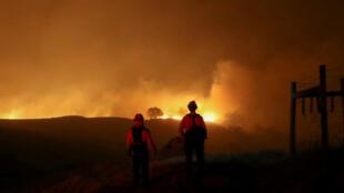 Dos bomberos miran un  incendio cerca a Geyserville, California, EE. UU., el 24 de octubre de 2019.