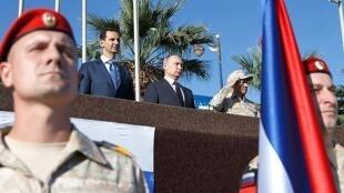 Vladimir Poutine et Bachar al-Assad assistent à un défilé dans une base militaire russe au nord-ouest de la Syrie, le 11 décembre 2017.
