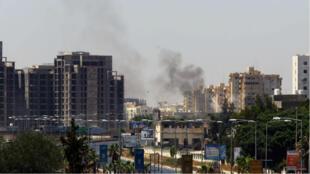 Une colonne de fumée s'élève au-dessus de la route de l'aéroport de Tripoli, dimanche, en Libye.