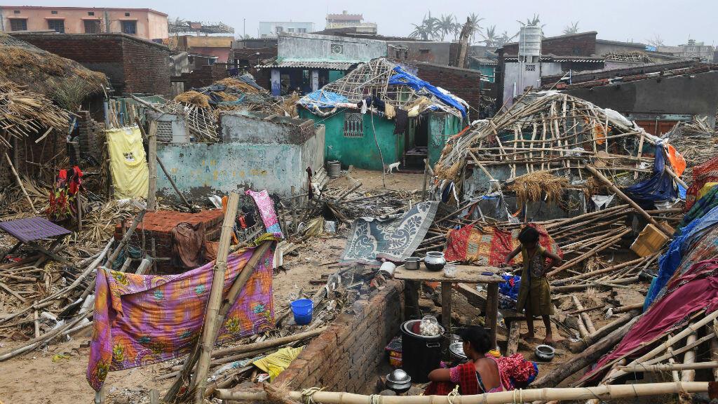 Una mujer india se sienta en los escombros con un niño en un edificio dañado por la tormenta en Puri, en el estado indio oriental de Odisha, el 4 de mayo de 2019.