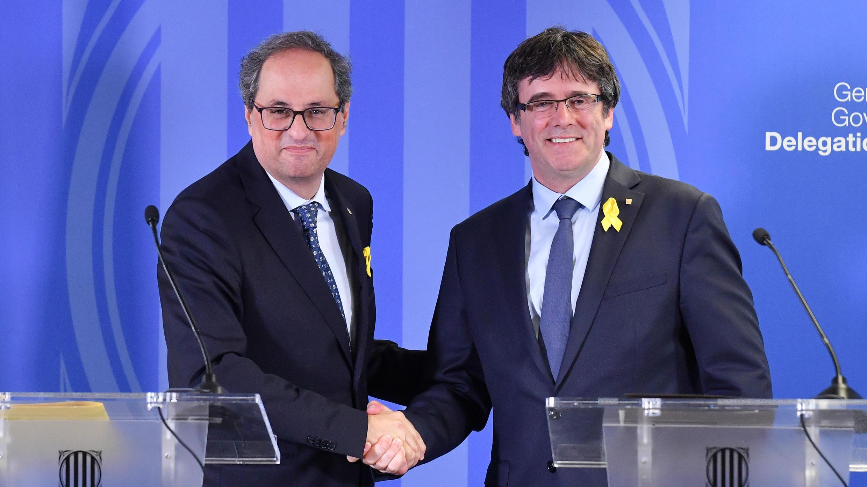 El expresidente regional de Cataluña, Carles Puigdemont, estrecha la mano del actual presidente Quim Torra, mientras dan una conferencia de prensa conjunta después de su reunión en Bruselas, el 28 de julio de 2018.