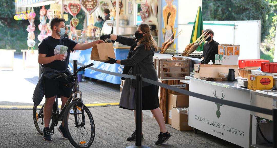 Un cliente visita un pequeño mercado bávaro donde compra alimentos. Landshut, Alemania , el 6 de mayo de 2020.