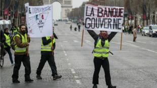 Manifestantes de los 'chalecos amarillos' sostienen carteles que contienen amenazas a los bancos. París, Francia, el 15 de diciembre de 2018.
