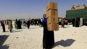 لاجئة سورية تحمل صناديق مساعدات في مخيم للاجئين الهاربين من البوكمال ودير الزور والميادين في 14 أكتوبر في بلدة العريشة في محافظة الحسكة السورية