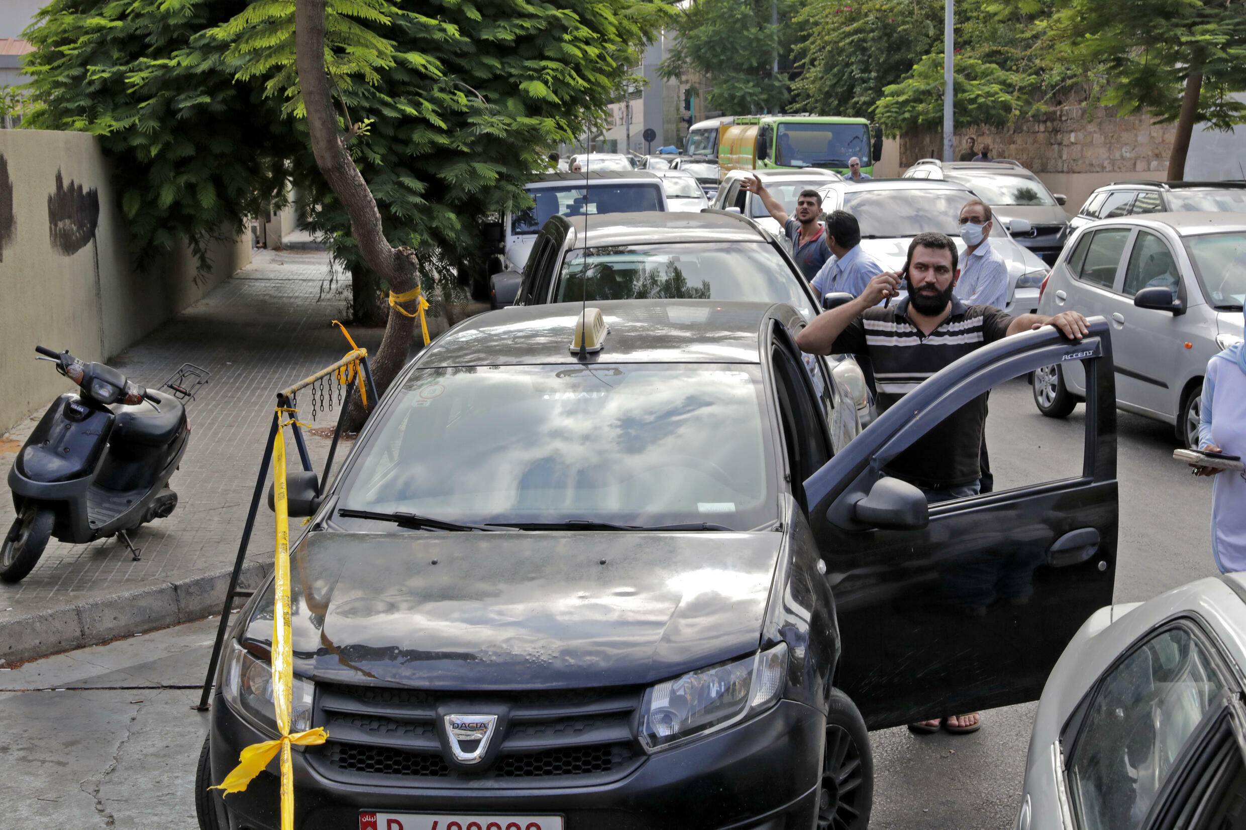 Lebanese wait in a queue outside a closed petrol station in the capital Beirut where an economic free fall has turned the country into a shell of its former self