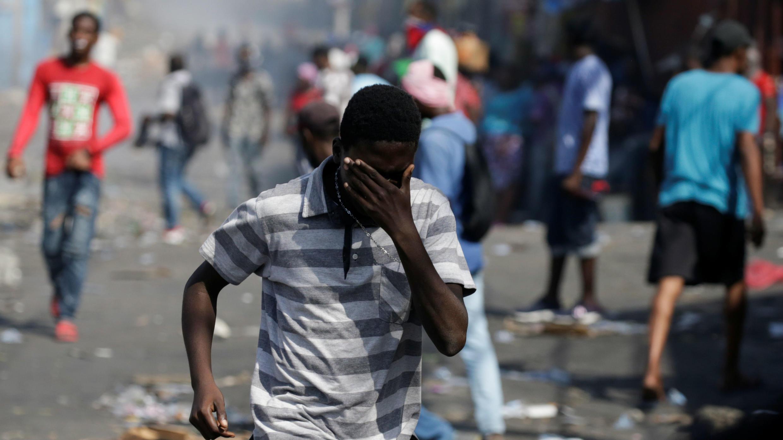 Un hombre se cubre la cara mientras corre durante una protesta para exigir la renuncia del presidente Jovenel Moïse, en las calles de Puerto Príncipe, Haití, el 11 de octubre de 2019.