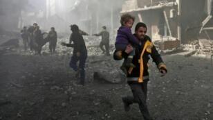 أحد عناصر الإنقاذ يحمل طفلا جريحا بعد انتشاله من تحت الأنقاض من مدينة حمورية في الغوطة الشرقية إثر تعرضها للقصف من قوات النظام في 19 شباط/فبراير 2018