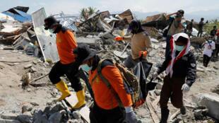 Miembros del equipo de rescate llevan un cadáver después de un terremoto que azotó el vecindario de Petobo en Palu, Indonesia, el 5 de octubre de 2018.