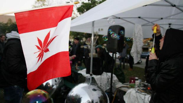 Un hombre juega con pompas de jabón cerca de una bandera canadiense con la hoja de arce cambiada a hoja de marihuana, el miércoles 17 de octubre de 2018, durante una celebración por la legalización de la marihuana,en el parque Trinity Belllwoods, en Toronto.