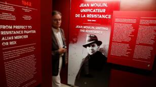 Un hombre camina junto a un retrato del líder de la Resistencia francesa Jean Moulin mientras visita el nuevo Museo de la Liberación de París.