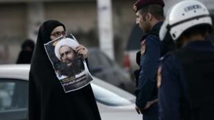 بحرينية تحمل صورة للشيخ نمر النمر خلال مواجهات مع الشرطة في المنامة 4 كانون الثاني/يناير 2016