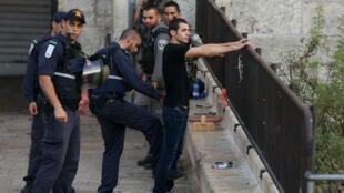 Des policiers israéliens controllent un jeune-homme dans Jérusalem-Est le 13 octobre 2015.