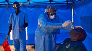 عضو من الفريق الخاص لوزارة الصحة في جنوب لسودان وهو يأخذ عينة من رجل خالط مصابا بكوفيد-19 في جوبا، 13 نيسان/أبريل 2020