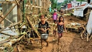 Des villageois tentent de circuler dans un des villages touchés par les inondations sur l'île de Samar, dans l'est des Philippines, le 16 décembre 2017.