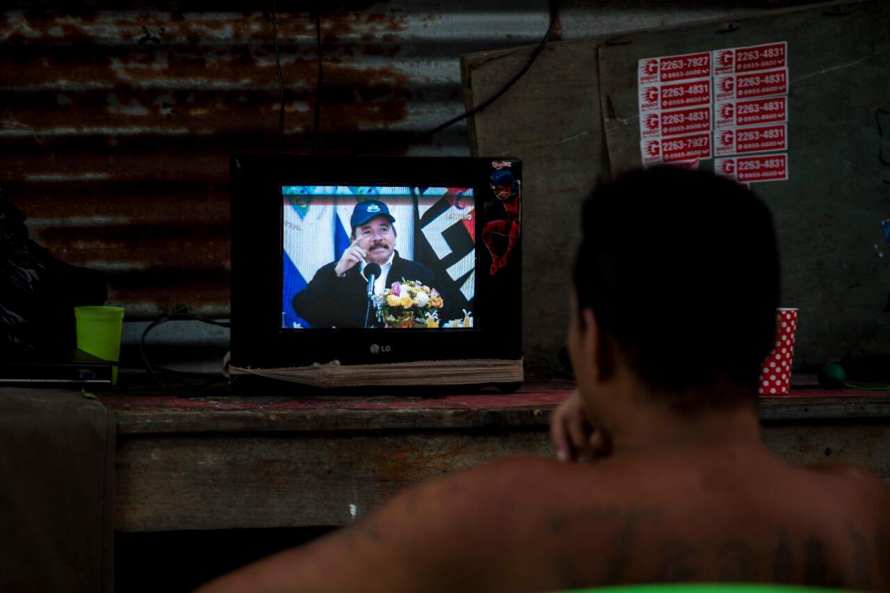 Un hombre observa la pantalla de un televisor en donde aparece el presidente de Nicaragua, Daniel Ortega, durante una transmisión de Cadena Nacional en Managua, Nicaragua, el 15 de abril de 2020.