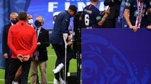 مهاجم باريس سان جرمان كيليان مبابي يستخدم عكازين للصعود الى منصة تتويج فريقه بلقب كأس فرنسا لكرة القدم، في 24 تموز/يوليو 2020.