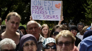 """A woman holds a placard reading """"We are all brothers and sisters"""" as she takes part in a silent march on July 30, 2016 in Lyon following the attack on a church in Saint-Etienne-du-Rouvray on July 26."""