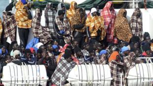 Des migrants sauvés en mer s'apprêtent à débarquer à Catane, en Sicile, le 21 mars 2017.