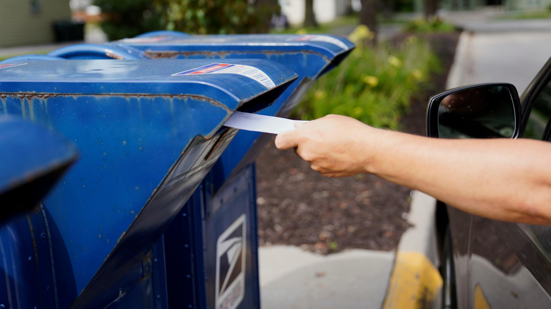 Un automovilista deja caer una carta en un buzón en Omaha, Nebraska, el martes 18 de agosto de 2020.