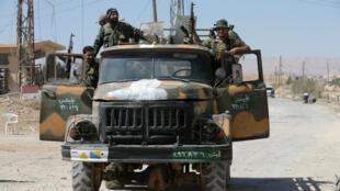 Des soldats de l'armée syrienne posent lors d'une patrouille, le 4 avril 2016, à Al-Qaryatain, une ville de la province de Homs.