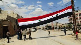 Le drapeau syrien hissé dans les rues de Douma après sa reprise par le régime syrien