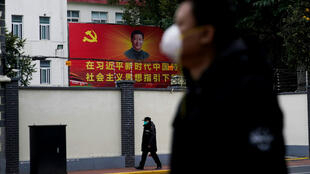 People wearing masks walk past a portrait of Chinese President Xi Jinping on a street as the country is hit by an outbreak of the novel coronavirus in Shanghai, China February 10, 2020.
