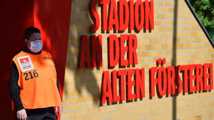 On guard: A volunteer wearing a face mask stands next to the entrance to the Alten Foersterei stadium prior to the Bundesliga match between Union Berlin and Bayern Munich
