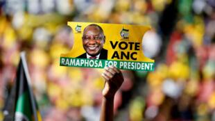Un sudafricano sostiene una pancarta con el rostro del presidente Cyril Ramaphosa. 5 de mayo de 2019.