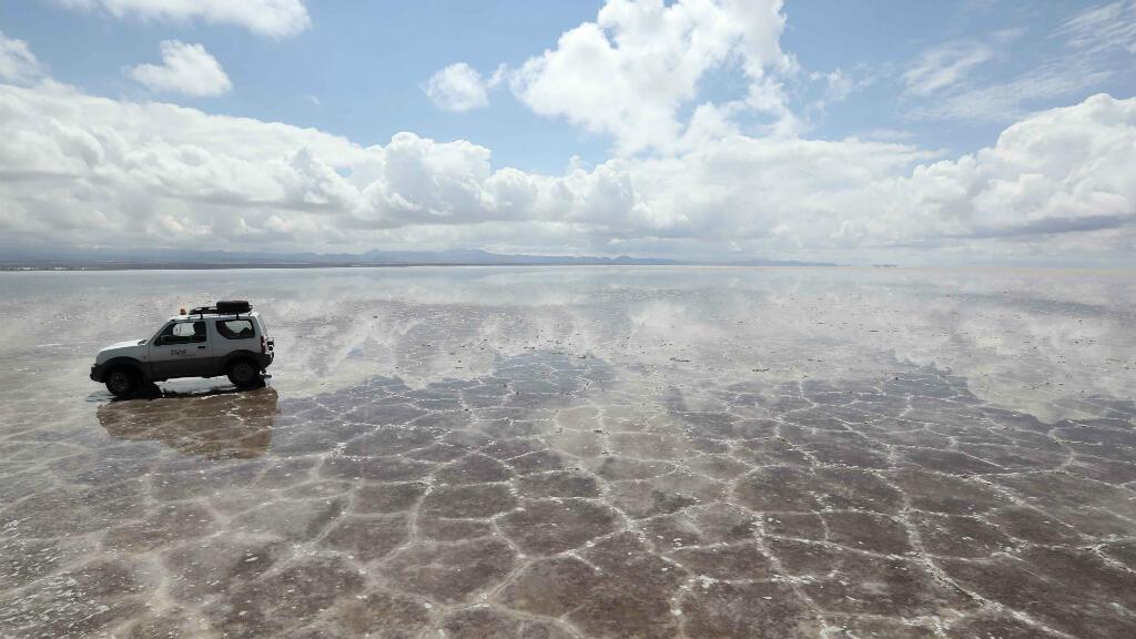 """Una camioneta circula por el salar de Uyuni tras las intensas lluvias de la noche, lo que provoca el famoso """"efecto espejo"""" por el reflejo del agua y la sal. El salar espera el paso del rally Dakar por la septima etapa, el sábado 13 de enero."""