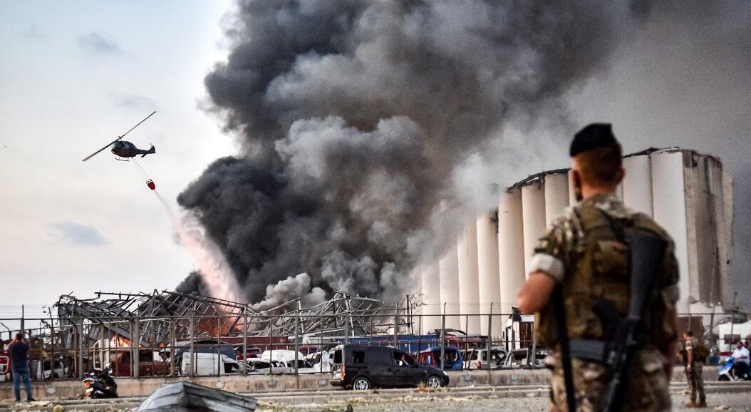 Soldados del ejército libanés rodean el área, mientras un helicóptero apaga un incendio en el lugar de una explosión en el puerto de Beirut, la capital del Líbano, el 4 de agosto de 2020.