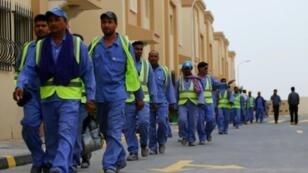 عمال يعودون من إحدى ورش البناء الخاصة بمونديال 2022 في الدوحة. 4 أيار/مايو 2015.
