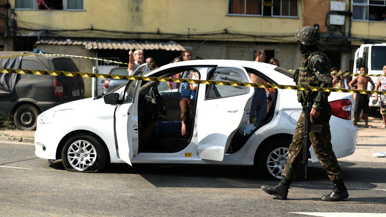 Un soldado del ejército camina cerca de un automóvil en el que murió un hombre durante un tiroteo militar, en Río de Janeiro, Brasil , el 7 de abril de 2019.