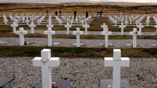 """Foto de archivo: Veteranos de la Guerra de las Malvinas Argentinas visitan el cementerio de Darwin, donde hay más de cien tumbas anónimas de soldados argentinos con la inscripción """"soldado argentino solo conocido por Dios""""."""