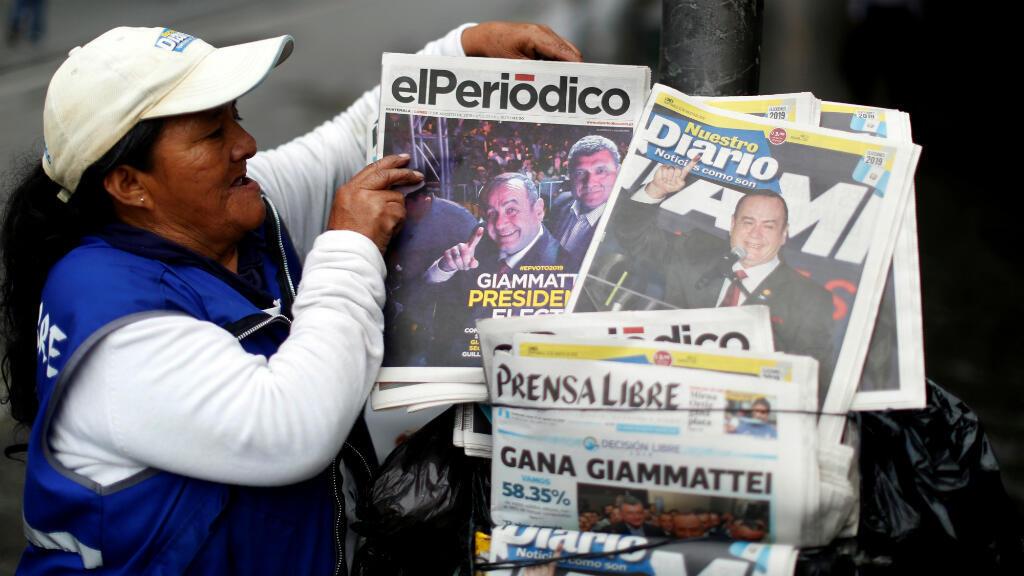 Una mujer vende periódicos con fotos del candidato presidencial Alejandro Giammattei, el ganador de la elección presidencial, en Ciudad de Guatemala, Guatemala,el 12 de agosto de 2019.