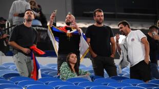 Des spectateurs patientent dans les tribunes de la Rod Laver Arena avant d'être expulsés en raison des restrictions d'accès liées à la pandémie de Covid-19, au cours du match du 3e tour entre le Serbe Novak Djokovic et l'Américain Taylor Fritz, lors de l'Open d'Australie de tennis, à Melbourne, le vendredi 12 février 2021.