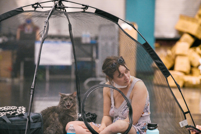 Una mujer y su gato descansan en una tienda de campaña en un centro refrigerado de la ciudad de Portland con motivo de una ola de calor, el 28 de junio de 2021 al noroeste de EEUU