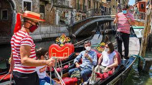The Venice gondoliers are back in business after Italy eased its virus lockdown, but can now only take on board five passengers at a time