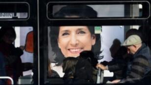 ركاب حافلة في تلبيسي يمرون أمام صورة سالومي زورابيشفيلي27 تشرين الثاني/نوفمبر 2018