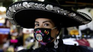 Una empleada de la empresa Trajes Típicos Jimy, que fabrica y distribuye vestimenta tradicional y de charros, posa con una máscara, en Guadalajara, México, el 6 de mayo de 2020