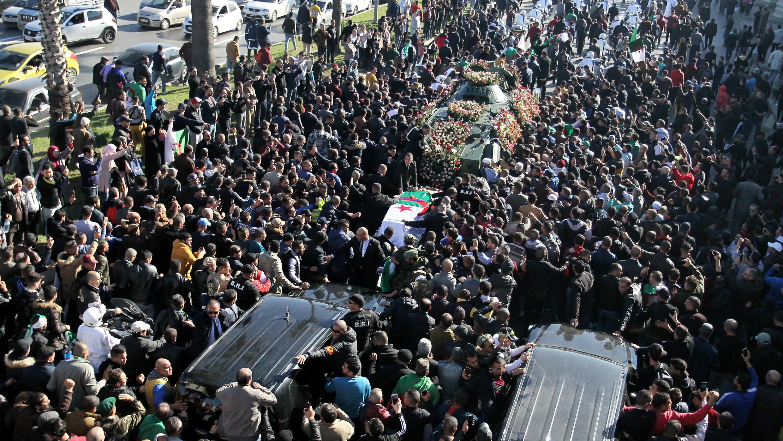 Una multitud camina en una procesión fúnebre de Ahmed Gaïd Salah en Argel, Argelia, el 25 de diciembre de 2019.