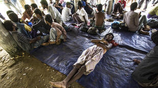 Migrants, at least some of whom are thought to be Rohingyas from Myanmar, wait at a shelter in Matang Raya village, Baktya, in northern Aceh on May 10, 2015 after being rescued at sea