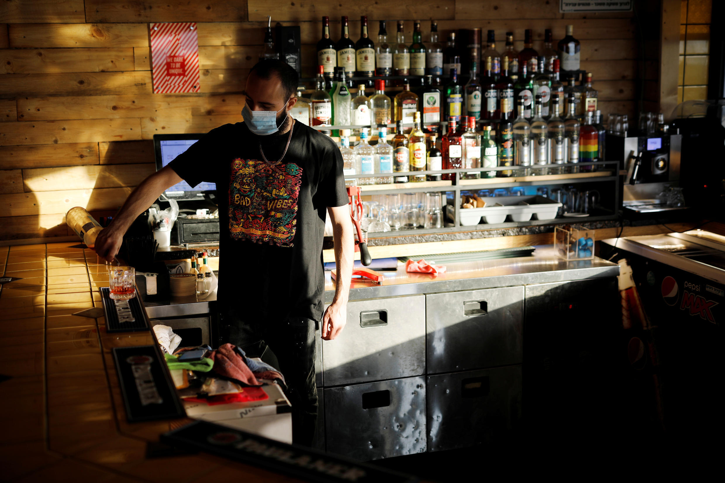 A masked bartender pictured on July 6 in Ashdod, Isreal, where authorities have ordered the immediate shuttering of bars and other social venues amid a spike in infections.